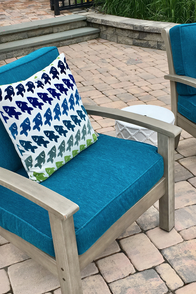 chair with blue cushions and a colorful accent pillow with wood frame
