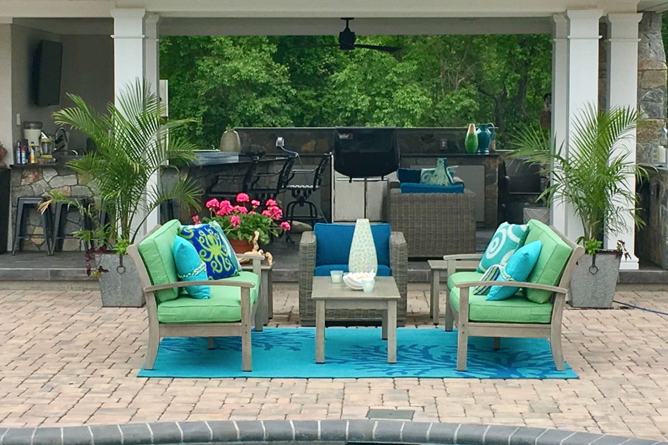 colorful furniture in front of an in-ground pool with exterior kitchen in background