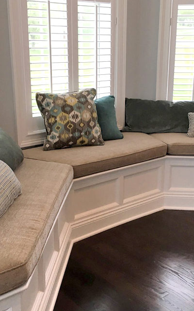 built in bench with pillows and white wooden window blinds